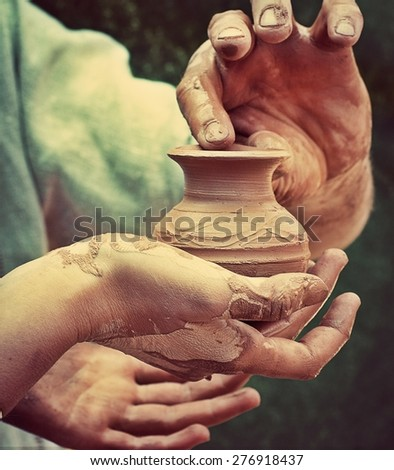 Close-up of hand holding pottery   jar - stock photo