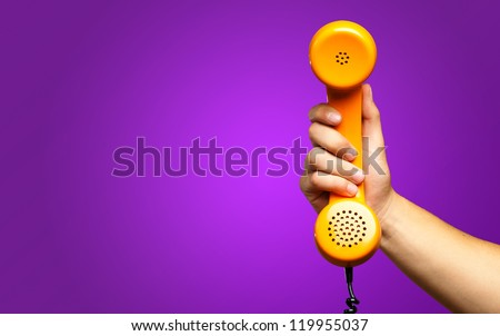 Close Up Of Hand Holding Telephone against a purple background - stock photo