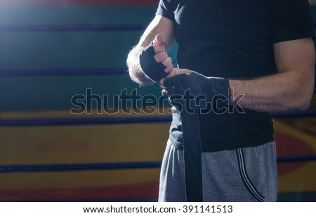 Close-up of hand of boxer who pulls wrist wraps before the fight or training. - stock photo