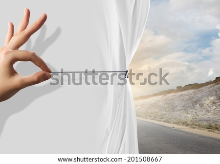 Close up of hand opening curtain with road behind it - stock photo