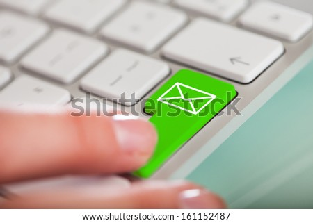 Close-up Of Hand Over Green Key With Email Sign On Keyboard - stock photo