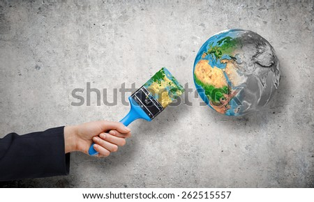 Close up of hand painting Earth planet with brush. Elements of this image are furnished by NASA - stock photo