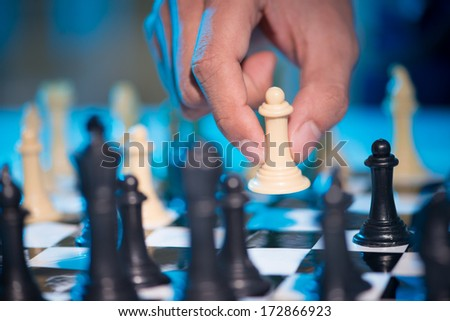 Close-up of hand playing chess - stock photo
