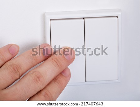 Close-up Of Hand Presses The Light Switch On The Wall - stock photo