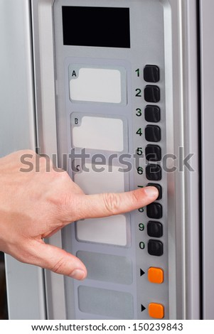 Close-up of hand pressing button of vending machine - stock photo