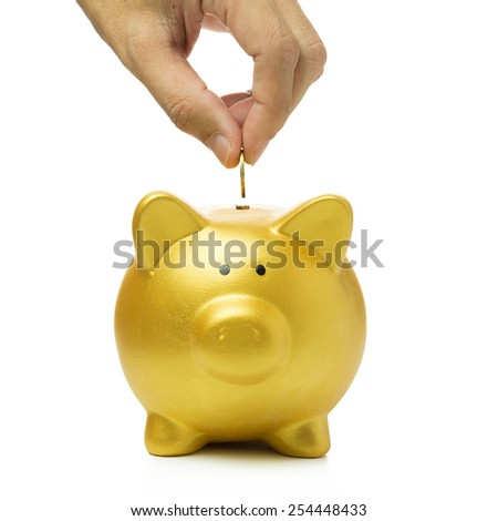 Close up of hand putting coin into golden piggy bank - stock photo
