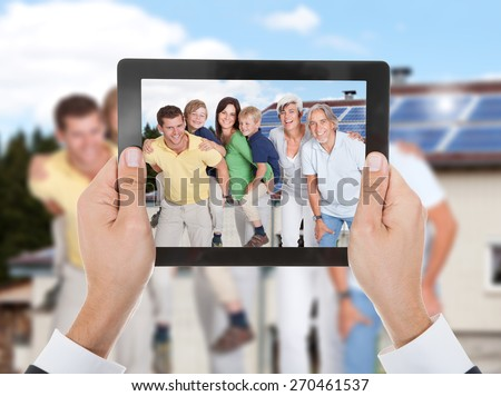 Close-up Of Hand Taking Photo Of Two Generation Family With Digital Tablet - stock photo