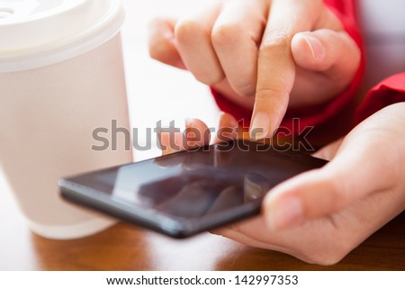 Close-up of hand using cell phone near disposable cup - stock photo