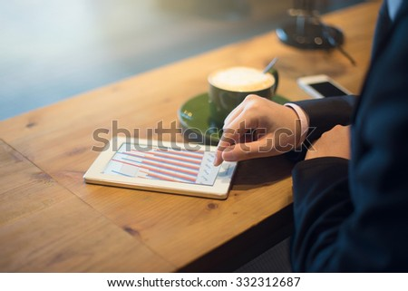 close up of hand using tablet computer at cafe - stock photo