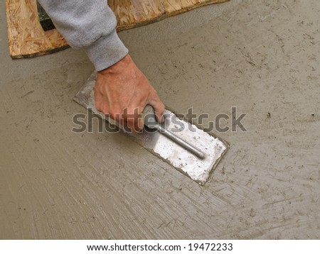 Close-up of hand using trowel to finish concrete slab - stock photo