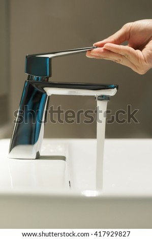 Close up of Hand with faucet and water flow on vanity basin in the bathroom. - stock photo