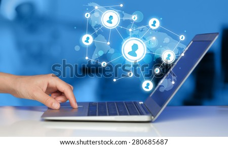Close up of hand with laptop and social media network icons - stock photo