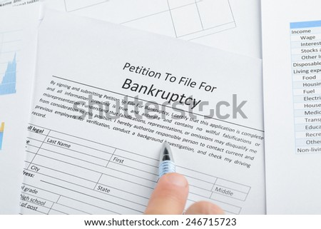 Close-up Of Hand With Pen On Bankruptcy Filing Petition Paper - stock photo
