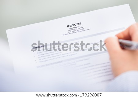 Close-up Of Hand With Pen Over Curriculum Vitae - stock photo