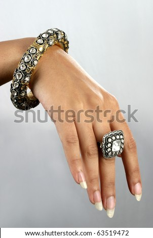 Close up of hand with traditional Indian diamond jewelery - stock photo
