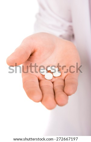 Close-up of hand with white pills, white background. - stock photo