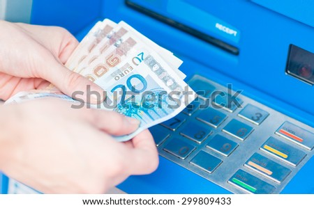 Close-up of hands counting Euro bills withdrawn from ATM. - stock photo