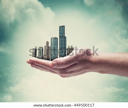 Close up of hands holding a modern cityscape - stock photo