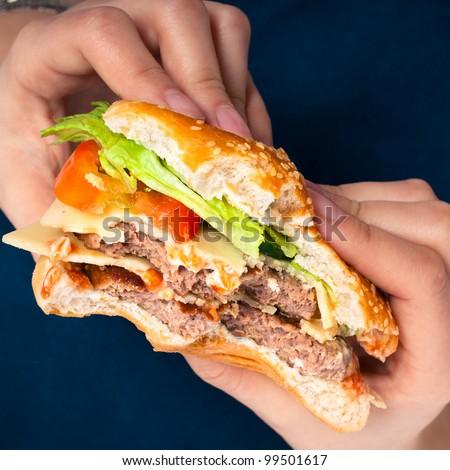 Close up of hands holding hamburger, over dark blue background. - stock photo