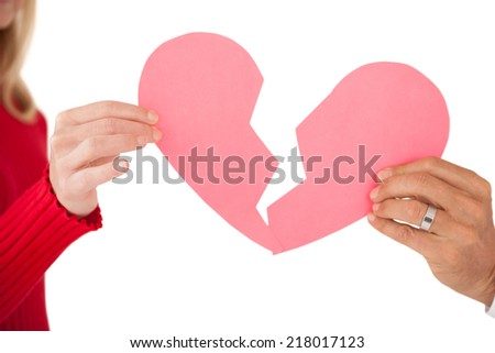 Close up of hands holding two halves of broken heart over white background - stock photo