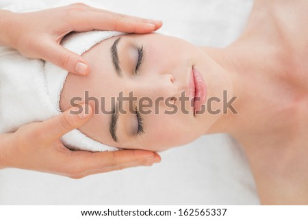 Close up of hands massaging a beautiful woman's forehead at beauty spa - stock photo