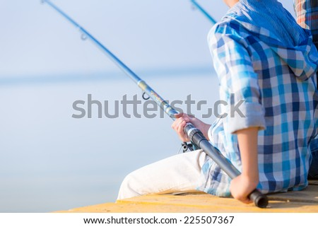 Close-up of hands of a boy with a fishing rod that is fishing on the pier - stock photo