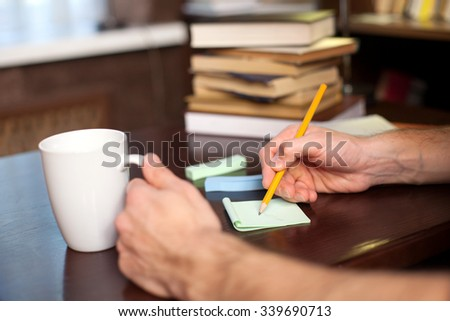 Close up of hands of a student writing down notes at the library. The man is sitting at the desk near books. He is drinking a cup of coffee - stock photo