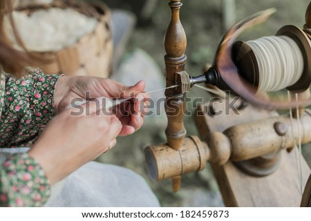 Close-up of hands of a woman traditional wool spinning. - stock photo