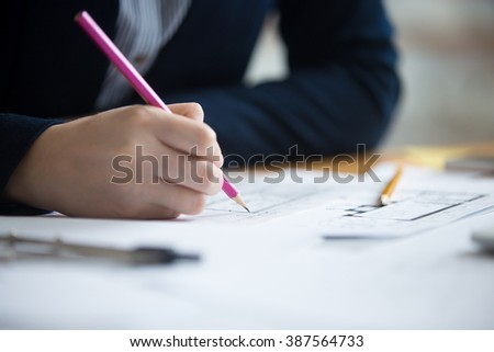 Close-up of hands of beautiful young designer woman wearing suit drawing draft using pencil. Attractive model working at office desk with blueprints for new project. Interior shot - stock photo