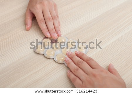 Close up of hands of doctor giving pills to woman. Their arms are on the table - stock photo