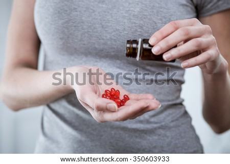 Close up of hands of druggie pouring out pills of ecstasy into her hand. The woman is standing - stock photo