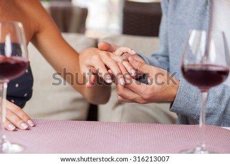 Close up of hands of man and woman dating in restaurant. The man is making proposal and wearing the gold ring on female finger. They are sitting and drinking red wine - stock photo