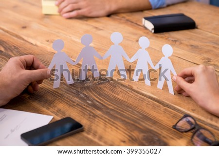 Close up of hands of man and woman holding paper people chain. Businesspeople holding paper man chain depicting solidarity and friendship. Closeup of symbol of unity and strength and togetherness.  - stock photo