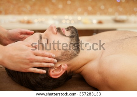 Close up of hands of masseuse massaging male head. The man is lying at spa. His eyes are closed with pleasure - stock photo