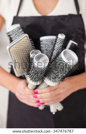 Close up of hands of professional female hairstylist holding a set of combs. She is standing at beauty salon - stock photo