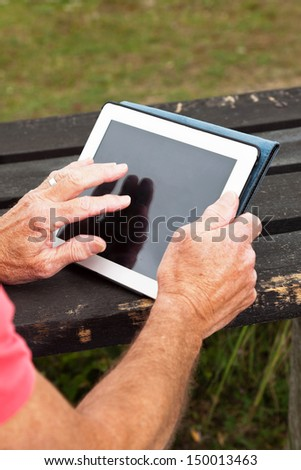 Close-up of hands of retired senior man resting and using his tablet at table in grass dune landscape. - stock photo
