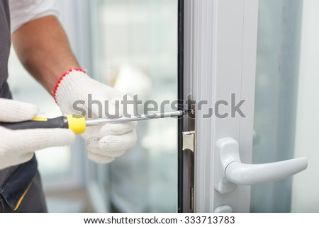 Close up of hands of young carpenter holding a screwdriver and fixing the lock of door. The man is standing in workwear - stock photo
