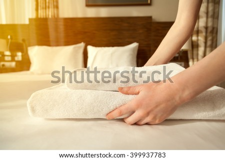Close-up of hands putting stack of fresh white bath towels on the bed sheet. Room service maid cleaning hotel room. Lens flair in sunlight - stock photo