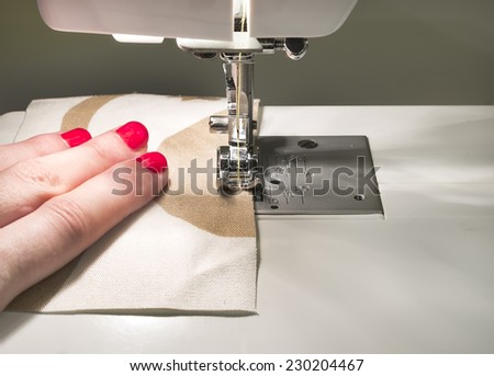Close-up of hands sewing on machine - stock photo
