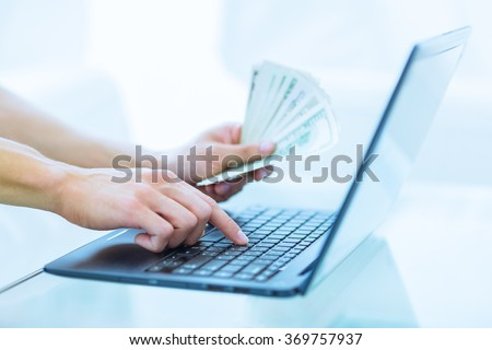 Close-up of hands shopping/paying online using laptop while holding US dollars.. - stock photo