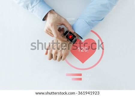 close up of hands with heart icon on smart watch - stock photo
