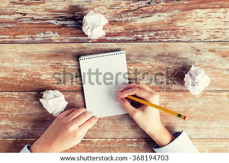 close up of hands with notebook and pencil - stock photo
