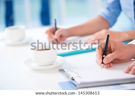 Close-up of hands writing something at the conference - stock photo