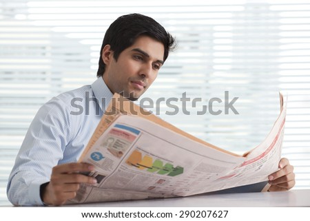 Close-up of handsome young business executive reading newspaper in office - stock photo