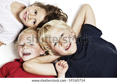 Close-up of happy children lying on floor in studio and looking up, isolated on white background, top view. - stock photo