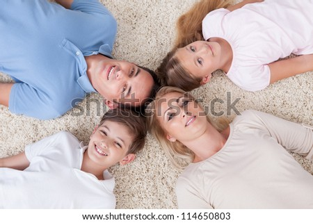 Close-up Of Happy Family Lying On Carpet Looking Up Heads Together At Home - stock photo