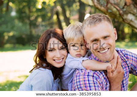 Close-up of happy family spending time together in the park. - stock photo