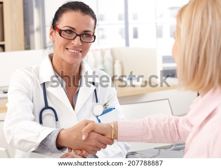 Close up of happy female brunette doctor at medical office with patient, wearing glasses, stethoscope and lab coat. Shaking hands, smiling. - stock photo