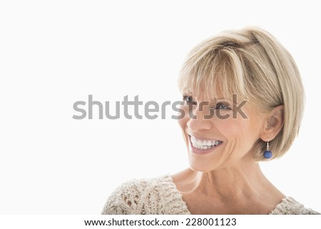 Close-up of happy mature woman looking away over white background - stock photo
