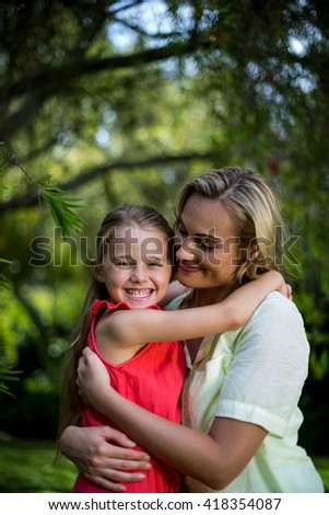 Close-up of happy mother embracing smiling daughter in yard - stock photo